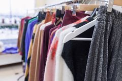 Fashion clothes on clothing rack. Trendy female wear. Fashion clothes on clothing rack - bright colorful closet. Closeup of trendy female wear on hangers in stock photos