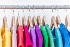 Fashion clothes on clothing rack colorful closet. Fashion clothes on clothing rack - bright colorful closet. Closeup of rainbow color choice of trendy female stock photos