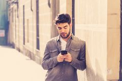 Young attractive happy stylish man on smart phone social network app in european city outdoors. Fashion college man in his twenties happy checking blog or stock photography