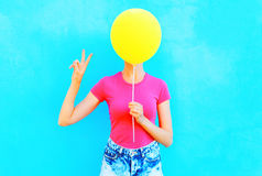 Fashion colorful woman is hiding her face a yellow air balloon having fun over blue background Stock Photo