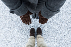 Fashion composition of Female brown gloves and male casual brown boots standing on asphalt covered gritty snow surface. Male and Female boots standing on asphalt Stock Photo