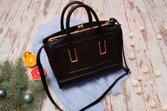Fashion concept. Black female bag, warm sweater on a wooden background Royalty Free Stock Image
