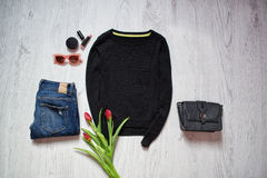 Fashion concept. Black sweater and tulips, blue jeans, black bag, sunglasses, lipstick. Spring wardrobe. Wooden background. Stock Photo
