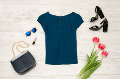 Fashion concept. Blue blouse, handbag, round glasses, lipstick, black shoes and pink tulips. Top view, light wood background.  stock photography