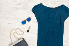Fashion concept. Blue blouse, round glasses, lipstick and part of handbag. Top view. Close up stock photos