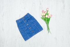 Fashion concept. Blue denim skirt and pink tulips. Wood background. ÑŽ stock image