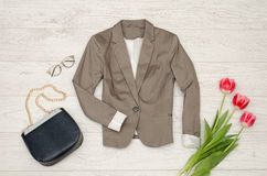 Fashion concept. Classic jacket, handbag, sunglasses and pink tulips. Top view, light wood background Stock Photos