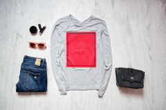 Fashion concept. Grey jacket with red rectangle, blue jeans, black bag, sunglasses, lipstick. Spring wardrobe. Wooden background. Stock Photos