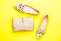 Fashion concept. Handbag, shoes isolated on yellow background, fashion. Top view. Pair of shoes and bag. Fashion and royalty free stock photography