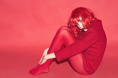 Fashion concept. Lady looking at camera and sits on floor. Woman with makeup and red wig posing in total red outfit. Girl on mysterious face in red formal stock photography