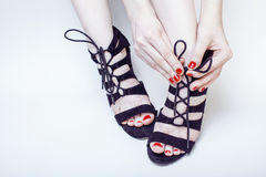 Fashion concept people: woman with red nails manicure pedicure tying shoelaces on hight heel shoes  on white Royalty Free Stock Photos