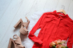Fashion concept. Red blouse and beige shoes on a light wooden background Stock Images
