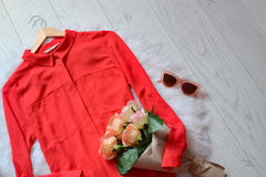 Fashion concept. Red blouse with a bouquet of roses and pink glasses on a light background. Stock Photo