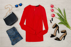 Fashion concept. Red blouse, jeans, handbag, sunglasses, black shoes, lipstick and pink tulips. Top view, light wood background Royalty Free Stock Photos