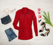 Fashion concept. Red blouse, jeans, handbag, sunglasses, black shoes, lipstick and pink tulips. Top view, light wood background Royalty Free Stock Photo
