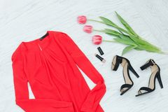 Fashion concept. Red blouse, shoes and pink tulips. Top view.  stock photo