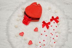 Fashion concept. Red box heart shaped with lace lingerie, white stockings with bows, heart shaped candles on a white fur Royalty Free Stock Photo