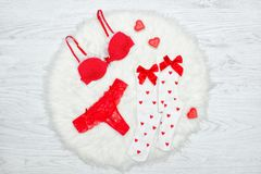 Fashion concept. Red bra, thongs and white stockings with bows,. Candles in the shape of a heart. White fur Royalty Free Stock Images