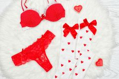 Fashion concept. Red bra, thongs and white stockings with bows,. Candles in the shape of a heart. White fur Royalty Free Stock Photography