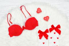 Fashion concept. Red bra and white stockings with bows, candles. In the shape of heart. White fur Stock Images