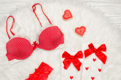 Fashion concept. Red bra and white stockings with bows, candles in the shape of a heart on a white fur. top view Stock Image