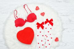 Fashion concept. Red bra, white stockings and box in the shape o. F heart. White fur Royalty Free Stock Image