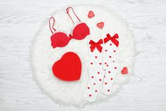 Fashion concept. Red bra, white stockings and box in the shape o. F heart. White fur Stock Photography