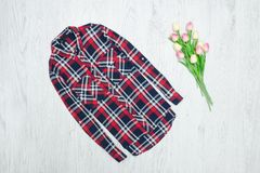 Fashion concept. Red checkered shirt and pink tulips. Wood background.  royalty free stock images