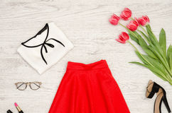 Fashion concept. Red skirt, blouse, sunglasses, lipstick, black shoes and pink tulips. Top view, light wood background Royalty Free Stock Photo