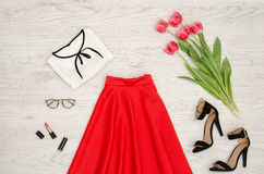 Fashion concept. Red skirt, blouse, sunglasses, lipstick, black shoes and pink tulips. Top view Stock Image