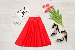 Fashion concept. Red skirt, blouse, sunglasses, lipstick, black shoes and pink tulips. Top view, light wood background Royalty Free Stock Photos