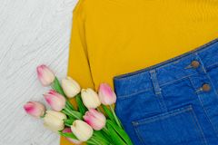 Fashion concept. Yellow sweater, blue skirt and pink tulips. Fashion concept. Yellow sweater, blue skirt and pink tulips stock photography