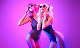 Fashion contemporary neon style. DJ girl dance. Fashion contemporary neon style. Two young graceful women in party DJ bodysuit dance. Disco 80s 90s summer vibes royalty free stock photography