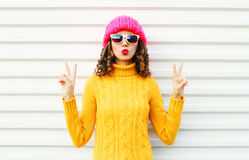 Fashion cool girl blowing red lips makes air kiss wearing colorful knitted yellow sweater hat over white Stock Photos
