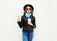 Fashion cool girl with coffee cup making air kiss red lips wearing black rock jacket over white Stock Photos
