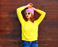 Fashion cool girl in colorful clothes over wooden background. Pink hat, yellow sweater royalty free stock photo