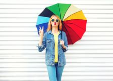 Fashion cool girl with colorful umbrella makes an air kiss on white. Background in city royalty free stock images