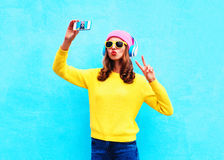 Fashion cool girl in headphones listening music taking photo makes self portrait on smartphone wearing colorful clothes over blue Stock Photos