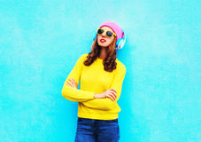 Fashion cool girl in headphones listening to music wearing colorful pink hat yellow sunglasses sweater over blue background Royalty Free Stock Images