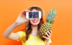 Fashion cool girl with pineapple taking picture self portrait on smartphone over colorful Stock Photo