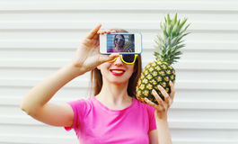Fashion cool girl with pineapple taking picture self portrait on smartphone Royalty Free Stock Photos