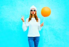 Fashion cool girl sends an air kiss holds balloon in white hat. On a blue background Royalty Free Stock Images