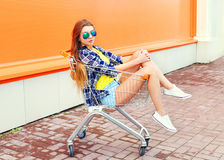 Fashion cool girl in shopping trolley cart with skateboard Royalty Free Stock Images