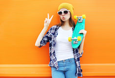 Fashion cool girl with skateboard having fun over colorful orange Stock Photos