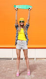 Fashion cool girl in sunglasses and colorful clothes, skateboard Royalty Free Stock Photos