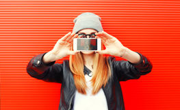 Fashion cool girl taking picture on smartphone self portrait, screen view, over red Stock Photography