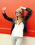 Fashion cool girl taking self-portrait on smartphone in Royalty Free Stock Photos