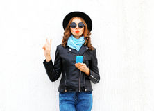Fashion cool girl using smartphone making air kiss blowing red lips wearing a black rock jacket hat over white. Background Stock Photo