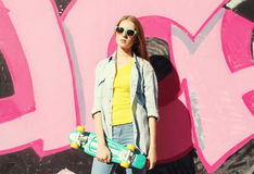 Fashion cool girl wearing a sunglasses, jeans shirt and skateboard Stock Images