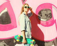 Fashion cool pretty girl wearing a sunglasses, jeans shirt and skateboard Stock Photography